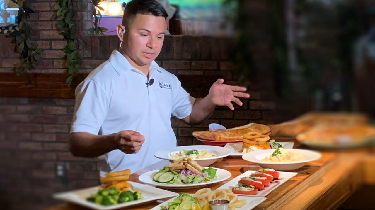 A chef showing off his prepared meals on a bar counter