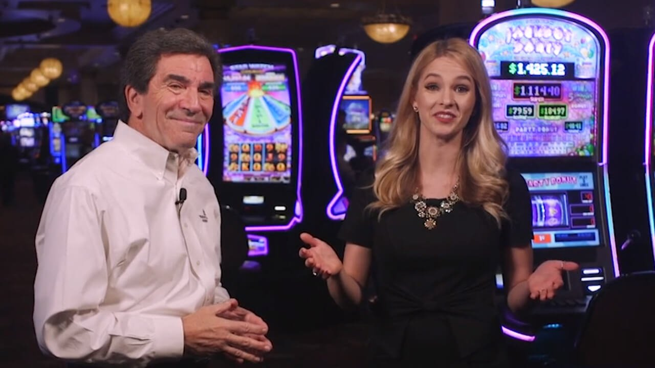 Two people standing in front of casino slot machines doing an interview